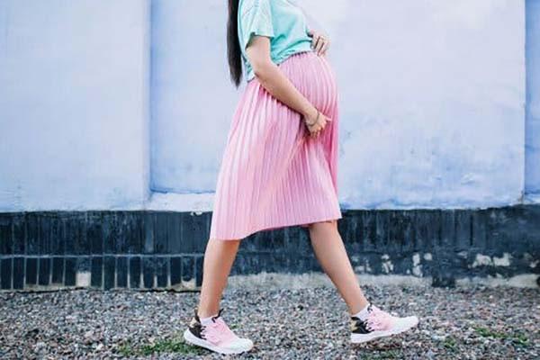 donna incinta con gonna rosa che cammina